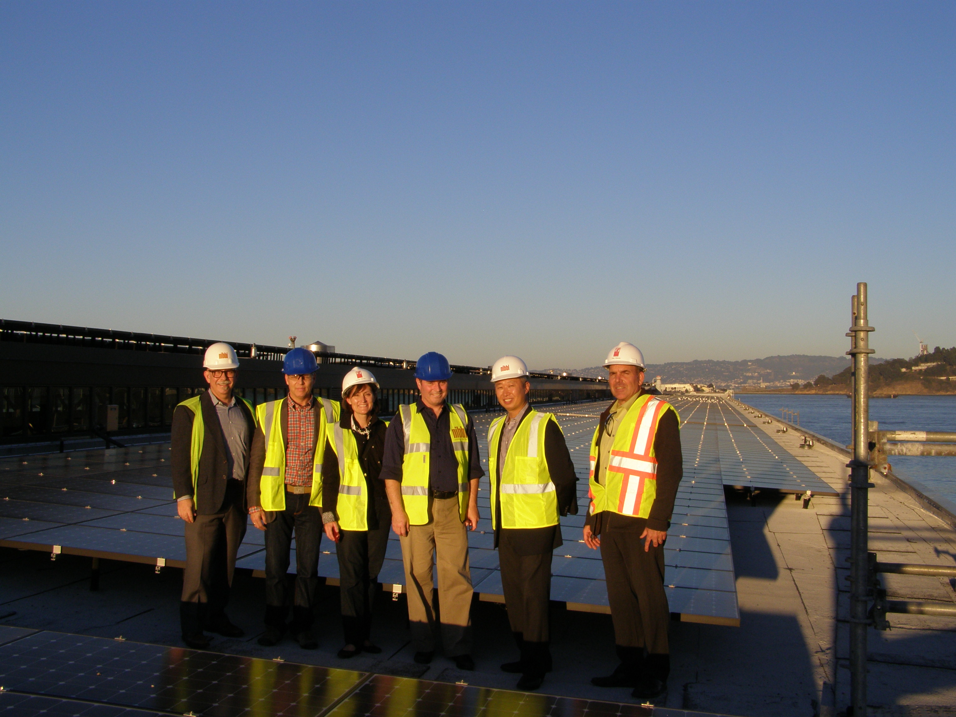 Applicants and federal and state tax credit reviewers inspecting solar panels on roof